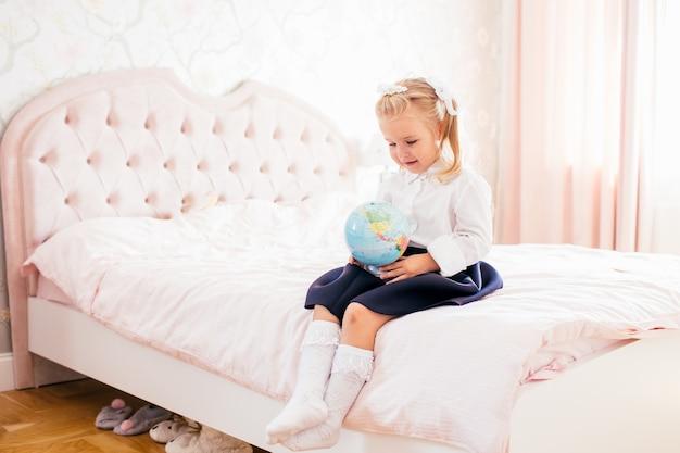 Mała urocza blondynki dziewczyna w mundurku szkolnym i białych golfach jest usytuowana na ber w jej sypialni z kulą ziemską w jej rękach