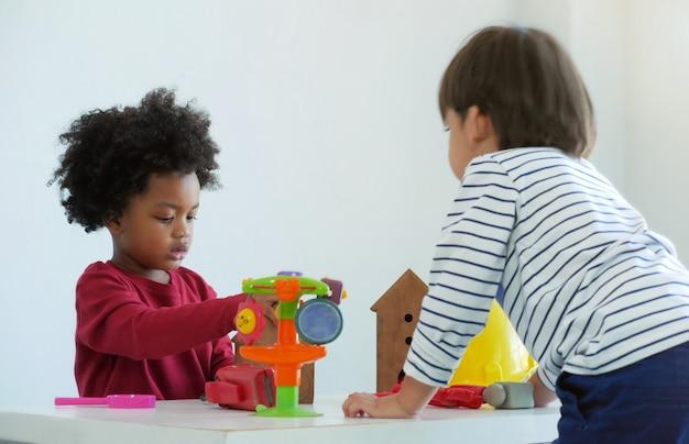 Mała urocza chłopiec bawić się zabawkę z przyjacielem w szkole. amerykanina afrykańskiego pochodzenia i przyjaciół pojęcie.