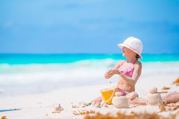 Mała urocza dziewczyna bawić się na plaży z piłką