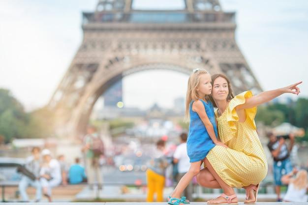 Mała urocza dziewczyna i jej młoda mama w paryżu w pobliżu wieży eiffla podczas letnich wakacji