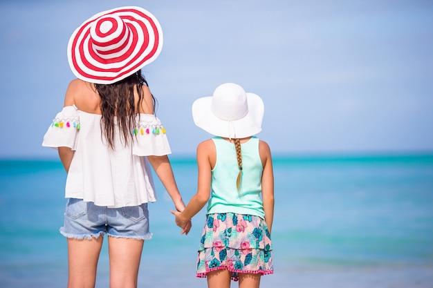 Mała urocza dziewczyna i potomstwo matka przy tropikalną plażą