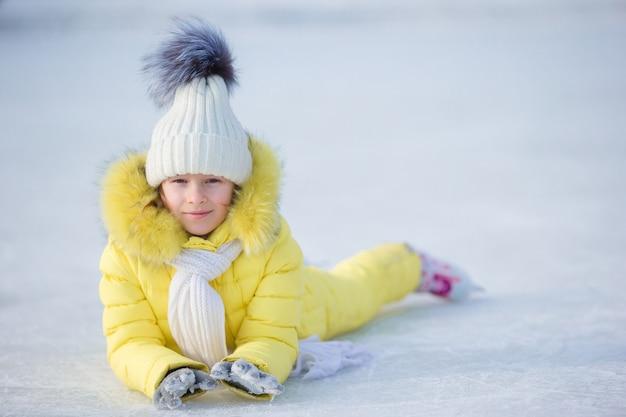 Mała urocza dziewczyna kłama na lodzie z łyżwami po spadku