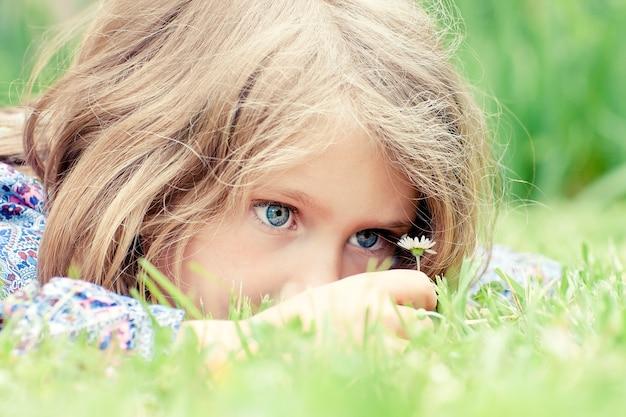 Mała urocza dziewczyna, leżąc na trawie patrząc na stokrotkę