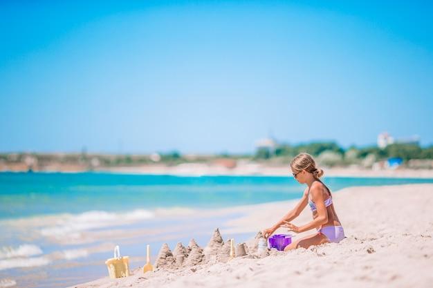 Mała urocza dziewczyna na tropikalnej plaży co zamek z piasku