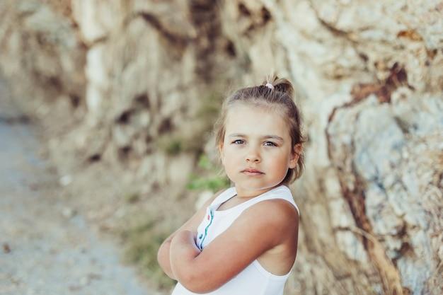 Mała urocza dziewczyna pozuje na zewnątrz