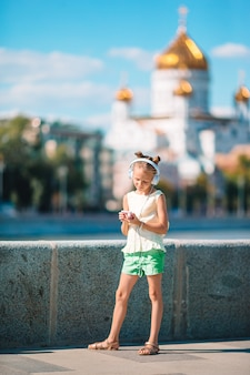 Mała urocza dziewczyna słucha muzykę w parku