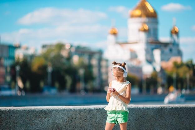 Mała urocza dziewczyna słuchająca muzyka w parku