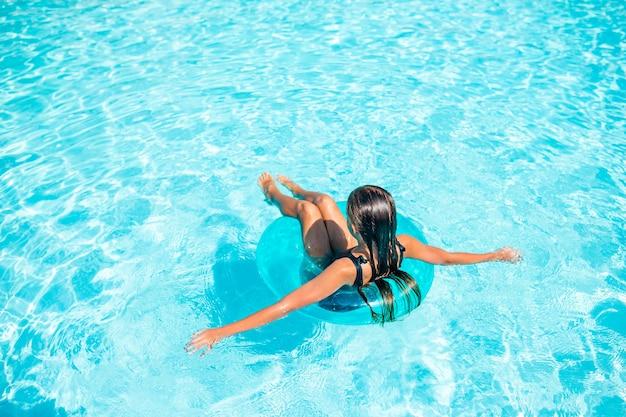 Mała urocza dziewczyna w plenerowym pływackim basenie