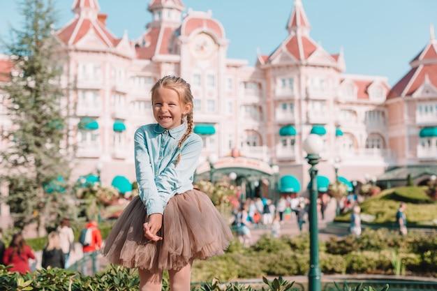 Mała urocza dziewczyna w sukni kopciuszka w bajkowym parku disneyland