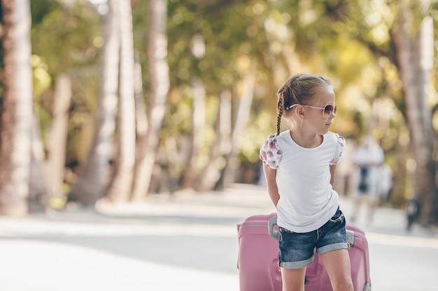 Mała urocza dziewczyna z dużym bagażem podczas wakacje