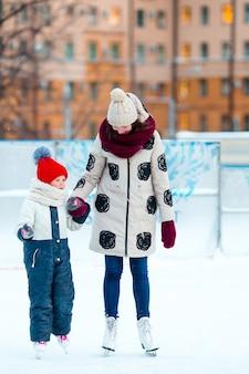 Mała urocza dziewczyna z macierzystym łyżwiarstwem na lodowisku z matką