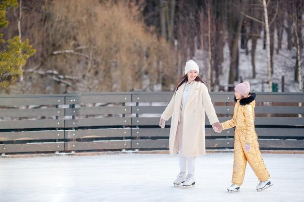 Mała urocza dziewczyna z matką jeździ na lodowisku
