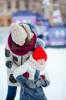 Mała urocza dziewczyna z matką jeździć na łyżwach na lodowisku