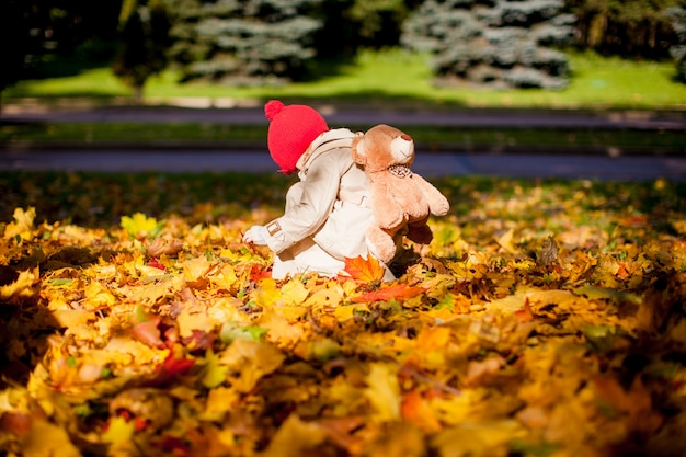 Mała urocza dziewczyna z niedźwiedziem plecakiem chodzi w lesie jesienią w piękny słoneczny dzień