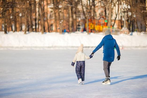 Mała urocza dziewczyna z ojcem uczy się jeździć na łyżwach na lodowisku