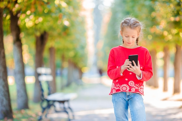 Mała urocza dziewczyna z smartphone w spadku. dzieciak zabawy w ciepły słoneczny jesienny dzień na zewnątrz