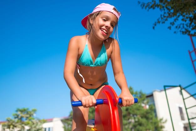 Mała urocza dziewczynka bawić się na koniu zabawka na placu zabaw w pobliżu morza w słoneczny ciepły letni dzień podczas wakacji. koncepcja zabaw dla dzieci na ulicy