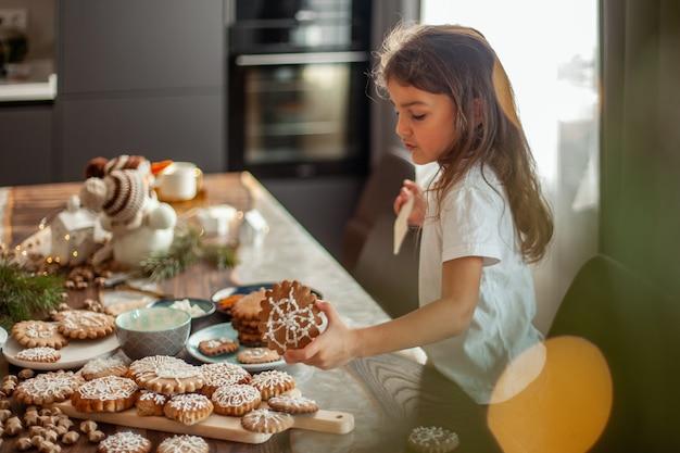 Mała urocza dziewczynka dekoruje pierniki z cukrowym lukrem przygotowującym na świąteczną koncepcję