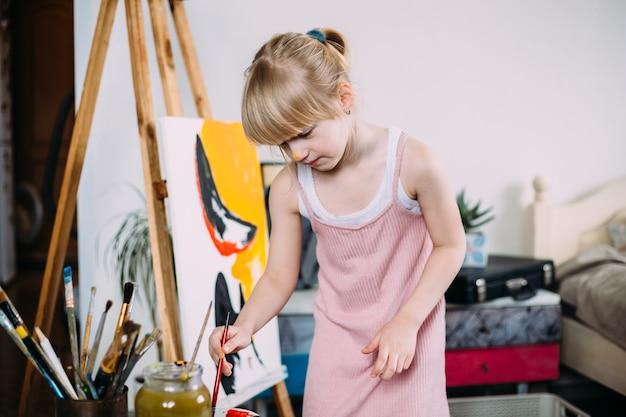Mała urocza dziewczynka maluje duży obraz akrylem w domu na sztalugach