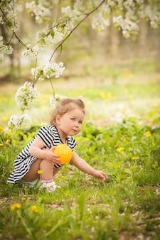 Mała urocza dziewczynka w ogrodzie, bawi się piłką