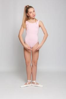 Mała urocza młoda baletnica wykonuje w domu pozy baletowe i ćwiczenia rozciągające na podłodze