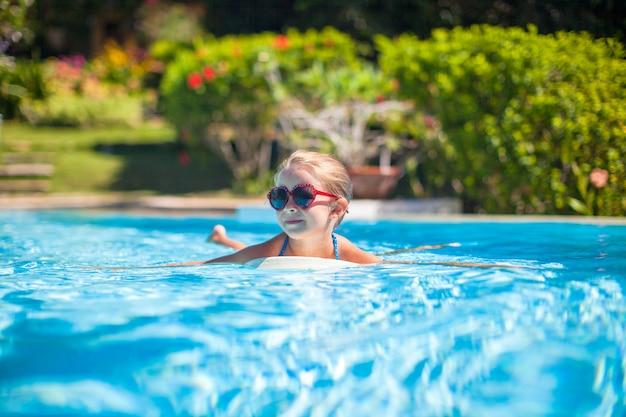 Mała urocza szczęśliwa dziewczyna pływa w pływackim basenie