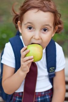 Mała urocza uczennica w mundurze siedzi na ławce i je jabłko