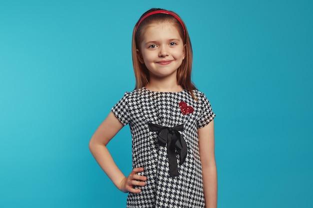 Mała urocza urocza dziewczynka uśmiecha się i trzyma jedną rękę w talii nad niebieską ścianą