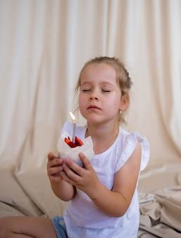 Mała urodzinowa dziewczynka trzyma babeczkę ze świeczką i składa życzenie na beżowym tle z miejscem na tekst