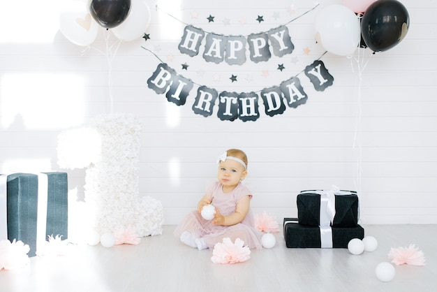 Mała urodzinowa dziewczynka w różowej sukience siedząca z dekoracjami z okazji urodzin na białym pokoju