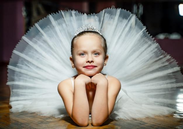 Mała uśmiechnięta balerina kłaść w tana studiu w białej spódniczce baletnicy