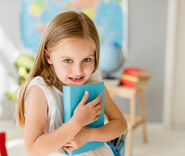 Mała uśmiechnięta blond dziewczyna trzyma błękitną książkę w szkolnej klasie