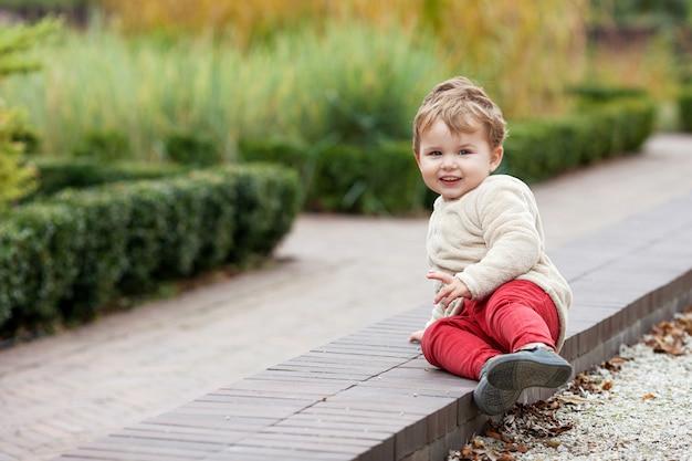 Mała uśmiechnięta chłopiec chodzi w parku. cudowne dziecko uśmiecha się i ma radość. zajęcia na świeżym powietrzu dla dzieci