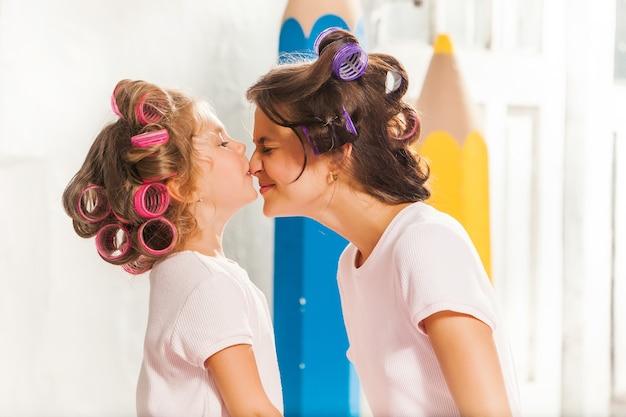 Mała uśmiechnięta dziewczyna bawi się z matką na białym tle