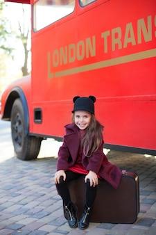 Mała uśmiechnięta dziewczyna blisko angielskiego autobusu w pięknym płaszczu z walizką. dziecko siedzi na walizce w pobliżu autobusu. londyn czerwony autobus. wiosna. jesień. podróż. londyn, anglia. mały podróżnik. szkolna przerwa