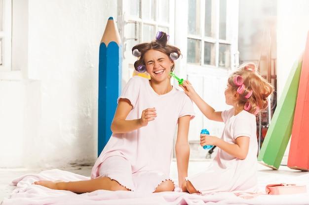 Mała uśmiechnięta dziewczyna gra z bańki i jej matką na białym tle