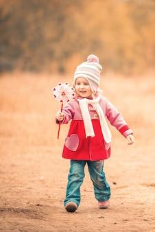 Mała uśmiechnięta dziewczyna na jesień krajobrazie