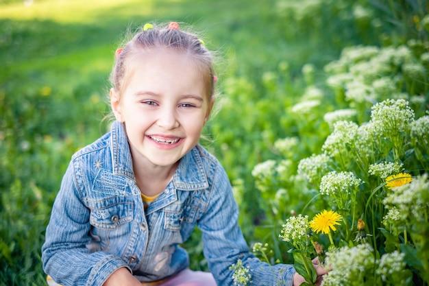 Mała uśmiechnięta dziewczyna siedzi w polu trawy