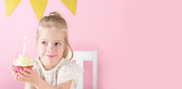 Mała uśmiechnięta dziewczyna trzyma ciastko ze świecą w dłoniach