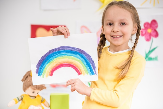 Mała uśmiechnięta dziewczyna trzyma obrazek w żółtym pulowerze.