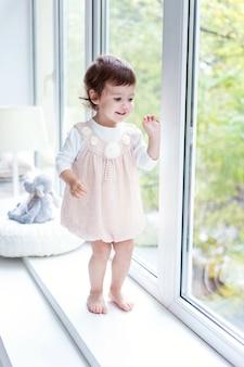 Mała uśmiechnięta dziewczyna w pastelowej różowej sukience stojącej na parapecie w jasnym świetle salonu w domu