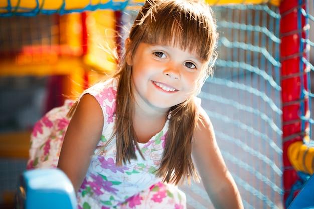 Mała uśmiechnięta dziewczyna w smokingowym obsiadaniu w kolorowych miękkich dekoracyjnych piłkach w pokoju zabaw