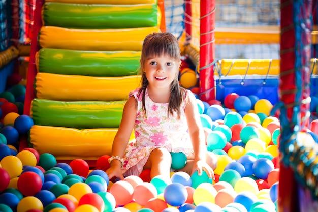 Mała uśmiechnięta dziewczyna w sukience siedzi w kolorowe miękkie kulki dekoracyjne w pokoju zabaw