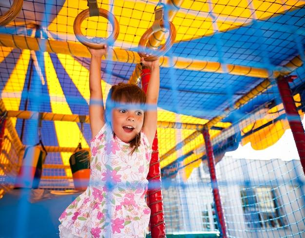 Mała uśmiechnięta dziewczyna w sukience wiszące na pierścieniach i podekscytowany w sali zabaw.