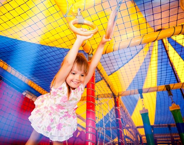 Mała Uśmiechnięta Dziewczyna W Sukience Wiszące Na Pierścieniach I Podekscytowany W Sali Zabaw. Premium Zdjęcia