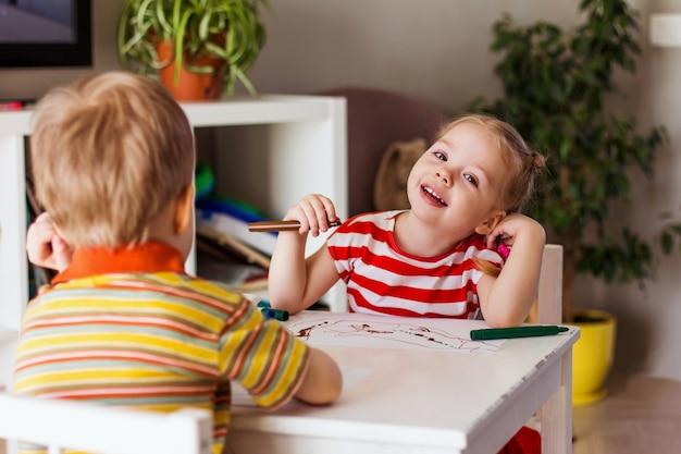 Mała uśmiechnięta dziewczynka i chłopiec 7 siedzą przy stole i rysują flamastrami