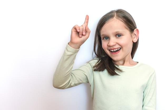 Mała uśmiechnięta dziewczynka na jasnym tle podniosła rękę i pokazała kciuk w górę