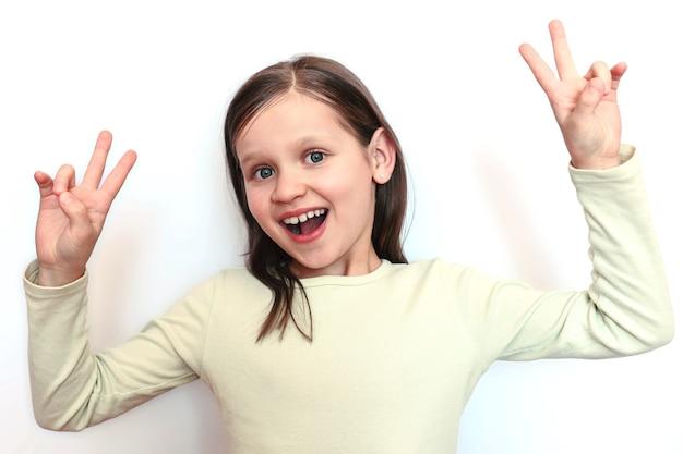 Mała uśmiechnięta dziewczynka na jasnym tle pokazuje dwie dłonie znak pokoju lub zwycięstwa