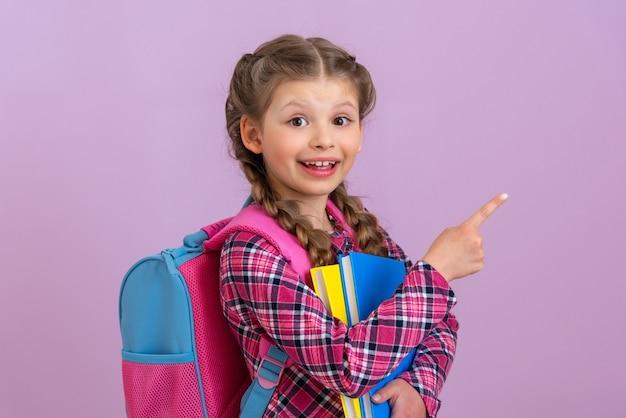 Mała uśmiechnięta dziewczynka wskazuje palcem na twoją reklamę na różowym, odizolowanym tle.
