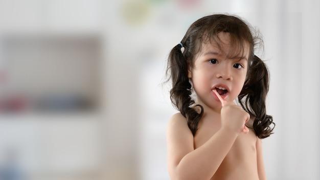 Mała uśmiechnięta kędzierzawa azjatycka dziewczyna szczotkuje zębu portret. dziecko dziewczynka uśmiechając się podczas mycia zębów. opieka zdrowotna, higiena jamy ustnej